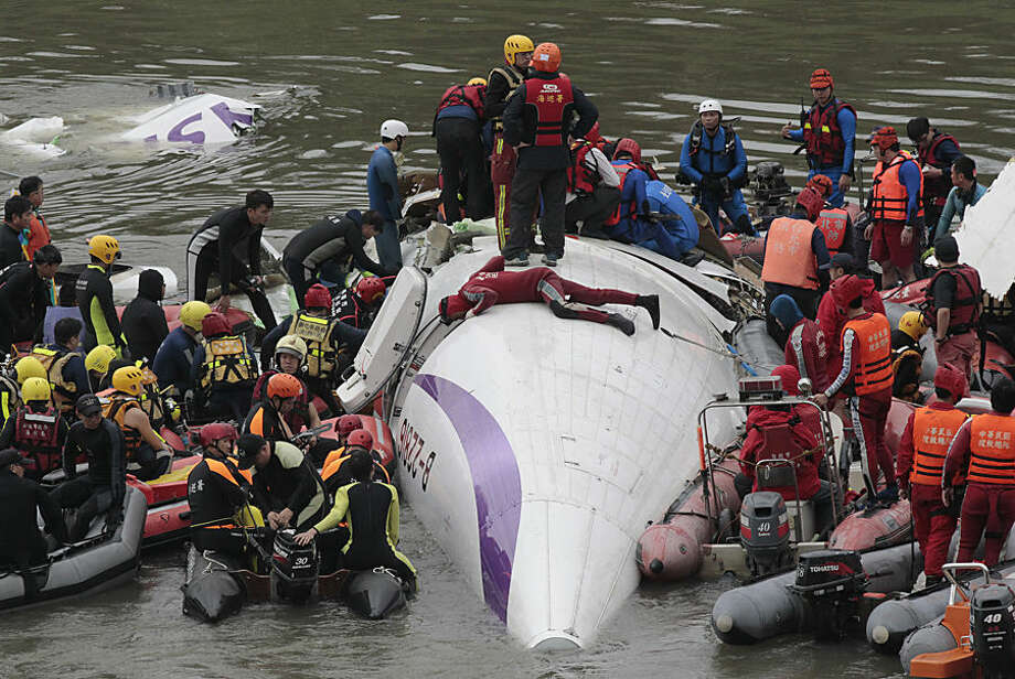 Emergency personnel try to extract passengers from a commercial plane after it crashed in Taipei, Taiwan, Wednesday, Feb. 4, 2015. The Taiwanese commercial flight with 58 people aboard clipped a bridge shortly after takeoff and crashed into a river in the island's capital on Wednesday morning. (AP Photo/Wally Santana)