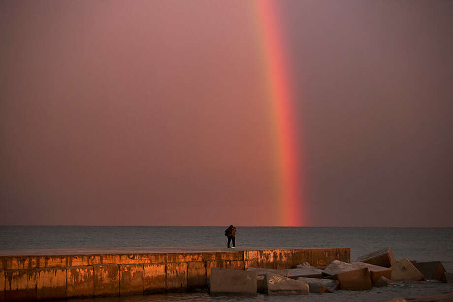 A couple kiss each other as a rainbow forms just after a storm at a breakwater facing the Mediterranean Sea in Barcelona, Spain, Wednesday, Feb. 4, 2015. (AP Photo/Emilio Morenatti)