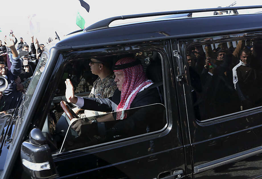 Jordan's King Abdullah II, returning from his trip to the U.S., greets as he drives through a crowd of people who were gathering to show their support at Queen Alia Airport in Amman, Jordan, Wednesday, Feb. 4, 2015. King Abdullah II rushed home Wednesday, cutting short a U.S. trip, to rally public support for even tougher strikes against the Islamic State group after the militants released a video showing the captured Jordanian pilot being burned to death in a cage. (AP Photo/Raad Adayleh)