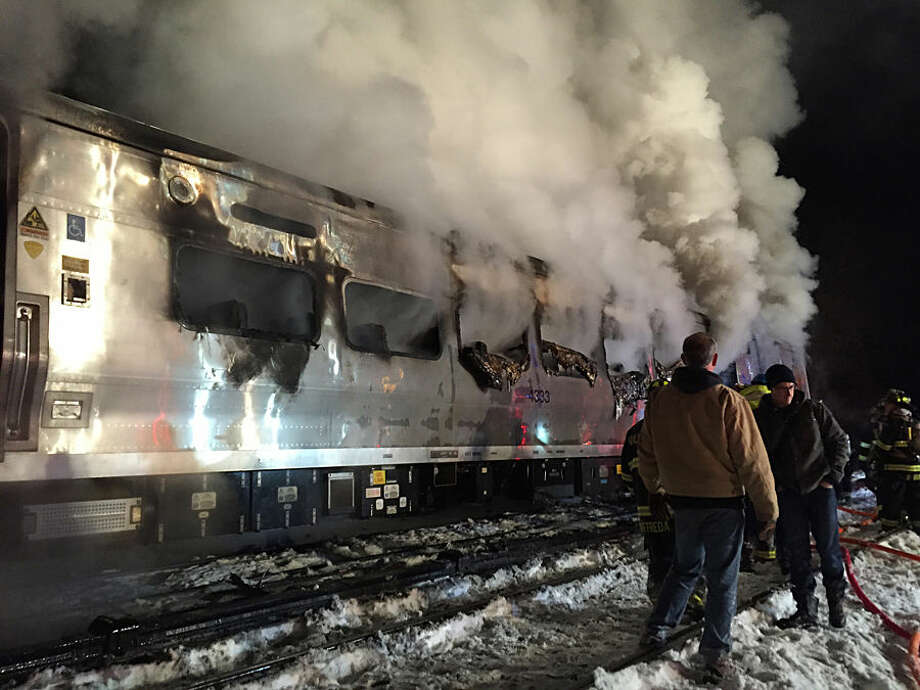 A Metro-North Railroad passenger train smolders after hitting a vehicle in Valhalla, N.Y., Tuesday, Feb. 3, 2015. (AP Photo/The Journal News, Frank Becerra Jr