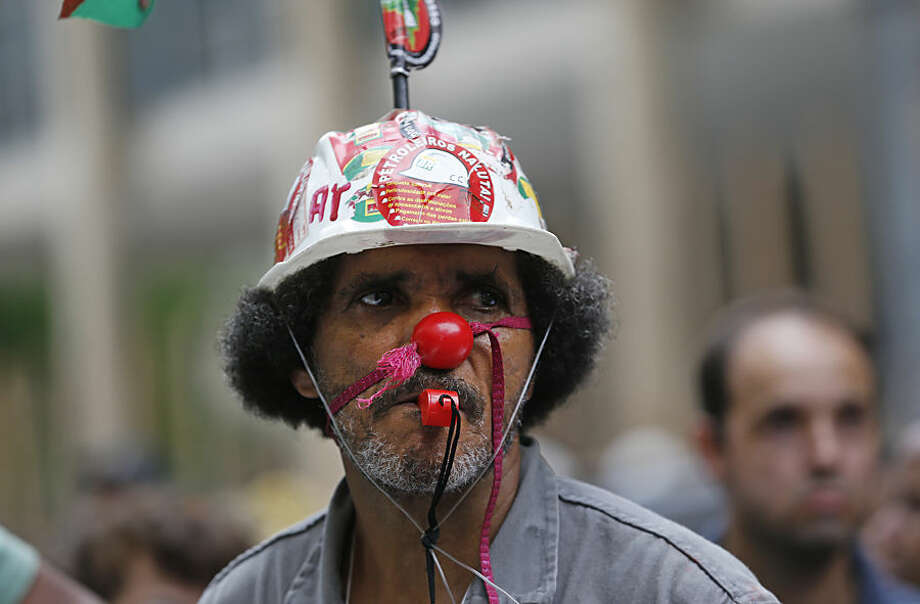 """A worker whose company is contracted by Brazil's government-run oil company Petrobras wears a helmet decorated with a sticker that reads in Portuguese """"Oil workers fight"""" to protest corruption and that he hasn't been paid, during a demonstration outside Rio's Justice Labor Court in Rio de Janeiro, Brazil, Wednesday, Feb. 4, 2015. Petrobras said Wednesday the company's chief executive officer and five other top figures stepped down amid a long-running and massive kickback scandal at the firm. (AP Photo/Silvia Izquierdo)"""