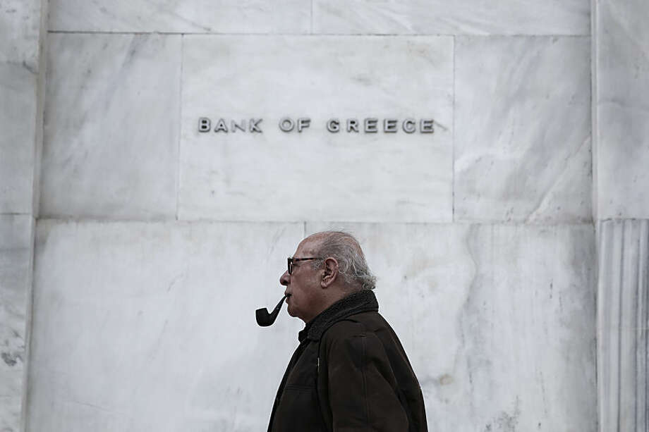 A man walks past the Bank of Greece headquarters, in central Athens, on Wednesday, Feb. 4, 2015. With all Europe waiting to see how Greece proposes to renegotiate its massive bailout loans, Greece's Prime Minister Alexis Tsipras and his Finance Minister Yanis Varoufakis are on a whirlwind tour of the region to discuss possible solutions. Tsipras wants easier terms of repayment on the 240 billion euros (currently $271 billion) in bailout loans and to ease back on the austerity budget measures the country has been required to make. (AP Photo/Petros Giannakouris )