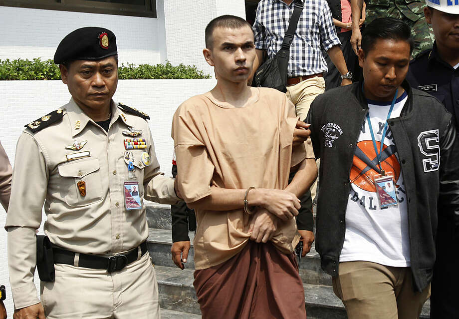 Thai correctional officers escort Bilal Mohammad, center, from a military court in Bangkok, Thailand, Tuesday, Feb. 16, 2016. Two foreigners, including Bilal, accused of carrying out a deadly bombing of a Bangkok landmark last year were brought to the military court Tuesday for the start of a highly anticipated trial that's been marred by one of the accused claiming he was tortured to elicit a confession. (AP Photo/Sakchai Lalit)