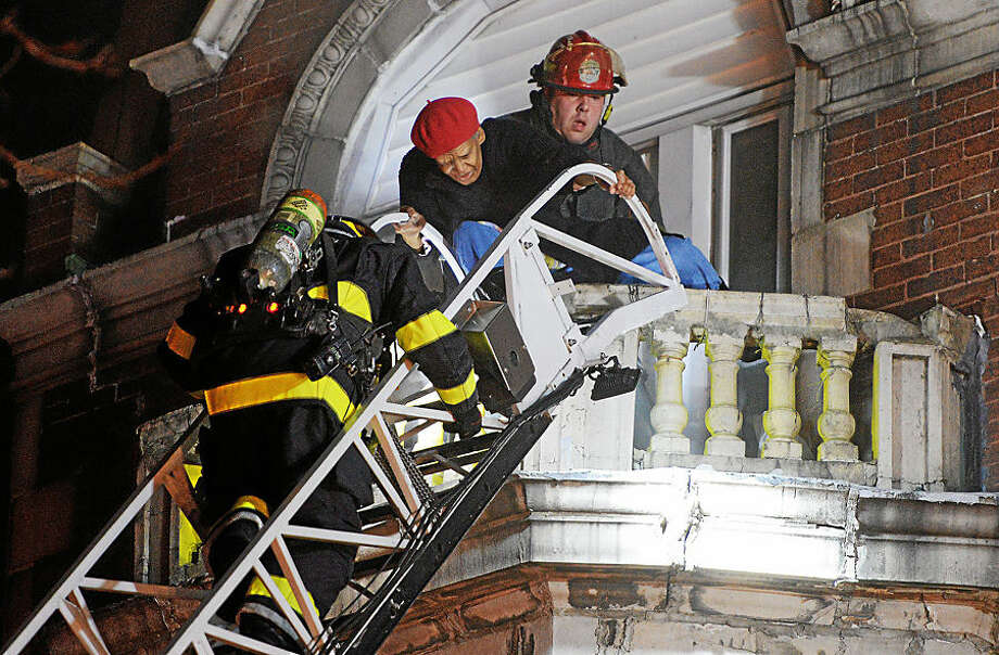 Firefighters rescue a person during a fire at the Norris Apartments building, Wednesday, Feb. 4, 2015, in Norristown, Pa. One resident died and at least three people were injured in the overnight fire that collapsed part of the 140-year-old apartment building. (AP Photo/The Times Herald, Tom Kelly IV)