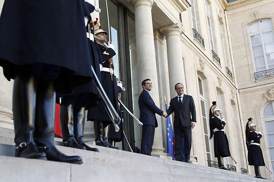Greece's Prime Minister Alexis Tsipras, center, is greeted by French President Francois Hollande before a meeting at the Elysee Palace, in Paris, France, Wednesday, Feb. 4, 2015. In a short trip to Brussels before heading to France, Tsipras was welcomed at the European Commission, one of the three main institutions overseeing Greece's finances, by President Jean-Claude Juncker. (AP Photo/Christophe Ena)