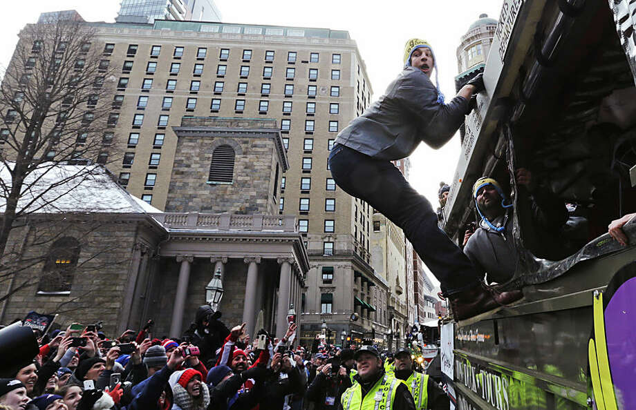 New England Patriots tight end Rob Gronkowski hangs out of a duck boat as fans cheer during a parade in Boston, Wednesday, Feb. 4, 2015, to honor the NFL football team's victory over the Seattle Seahawks in Super Bowl XLIX in Glendale, Ariz. (AP Photo/Charles Krupa)