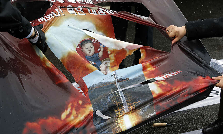 South Korean protesters tear a banner showing a picture depicting North Korean leader Kim Jong Un, center, during a rally to support President Park Geun-hye's policy about the Kaesong industrial park in Seoul, South Korea, Tuesday, Feb. 16, 2016. North Korea channeled about 70 percent of the money it received for workers at the now-shuttered Kaesong industrial park into its weapons programs and to buy luxury goods for the impoverished nation's tiny elite, South Korea said Sunday. (AP Photo/Lee Jin-man)