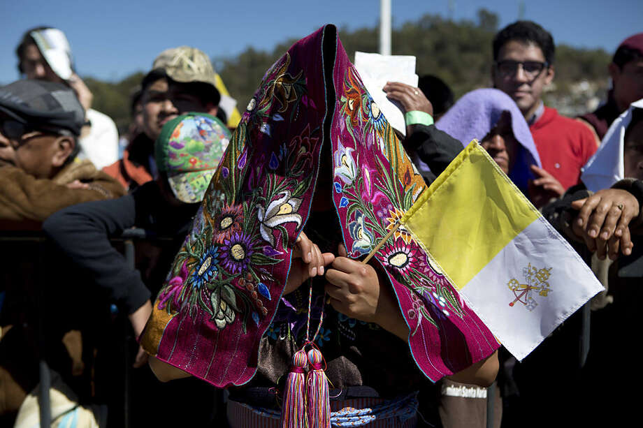 An indigenous woman holding a Vatican flag uses her traditionally embroidered shawl to shade herself during Mass with Pope Francis in San Cristobal de las Casas, Mexico, Monday, Feb. 15, 2016. Francis is celebrating Mexico's Indians on Monday with a visit to Chiapas state, a center of indigenous culture, where he will preside over a Mass in three native languages thanks to a new Vatican decree approving their use in liturgy. The visit is also aimed at boosting the faith in the least Catholic state in Mexico. (AP Photo/Eduardo Verdugo)