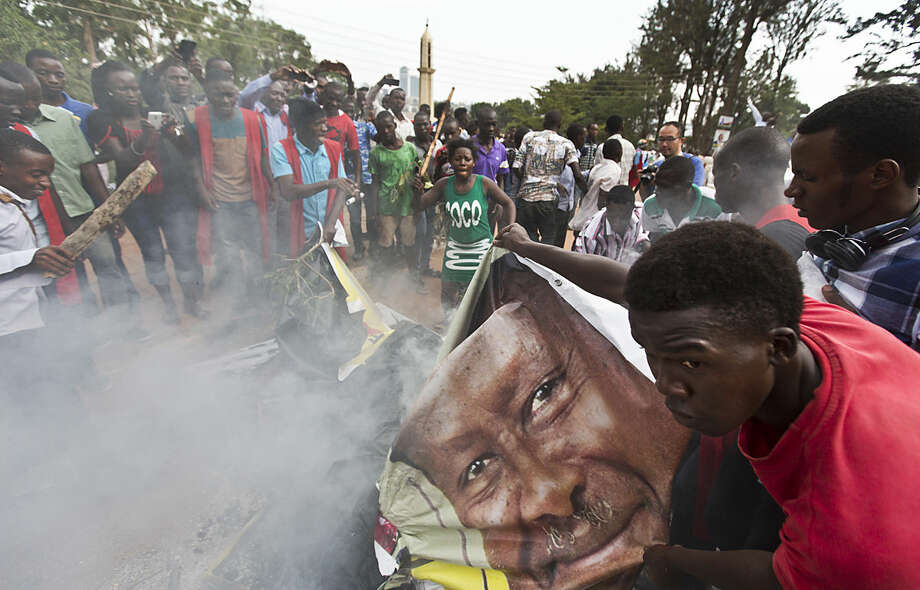 Student supporters of opposition leader Kizza Besigye burn posters of long-time President Yoweri Museveni, as they await the arrival of Besigye for a rally at the Makerere University in Kampala, Uganda, Monday, Feb. 15, 2016. Ugandan police fired tear gas and rubber bullets to break up the crowd of opposition supporters and briefly arrested Besigye himself on Monday, raising tensions ahead of elections widely seen as close. (AP Photo/Ben Curtis)