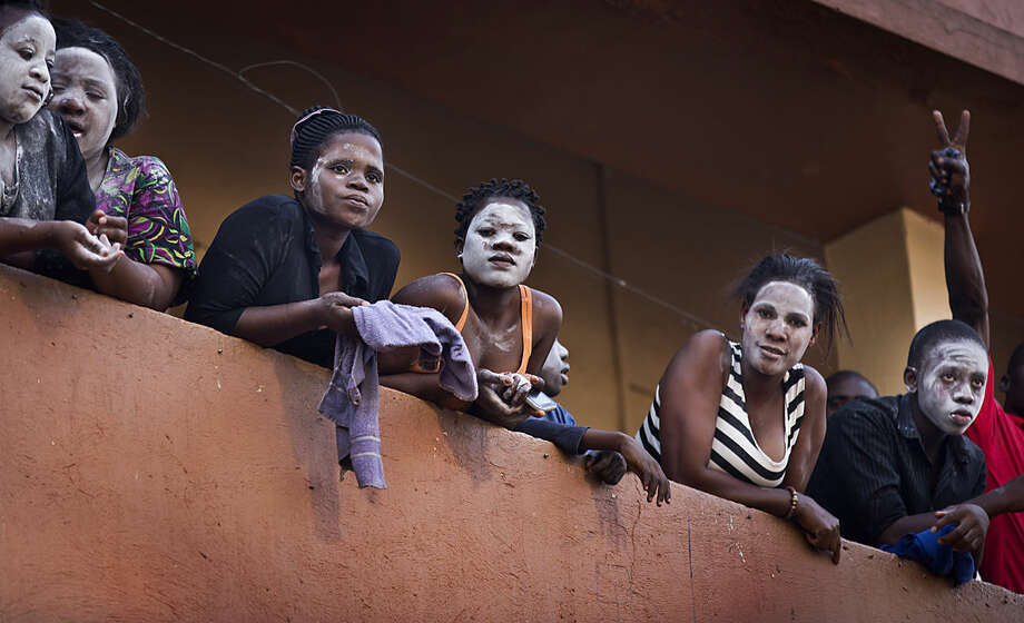 Residents on a balcony wear a white substance on their faces to protect against tear gas as they watch riot police chase angry supporters of opposition leader Kizza Besigye below, after he was prevented by police from reaching one of his campaign rallies, near to the Makerere University in Kampala, Uganda Monday, Feb. 15, 2016. Ugandan police fired tear gas and rubber bullets to break up the crowd of opposition supporters and briefly arrested Besigye himself on Monday, raising tensions ahead of elections widely seen as close. (AP Photo/Ben Curtis)