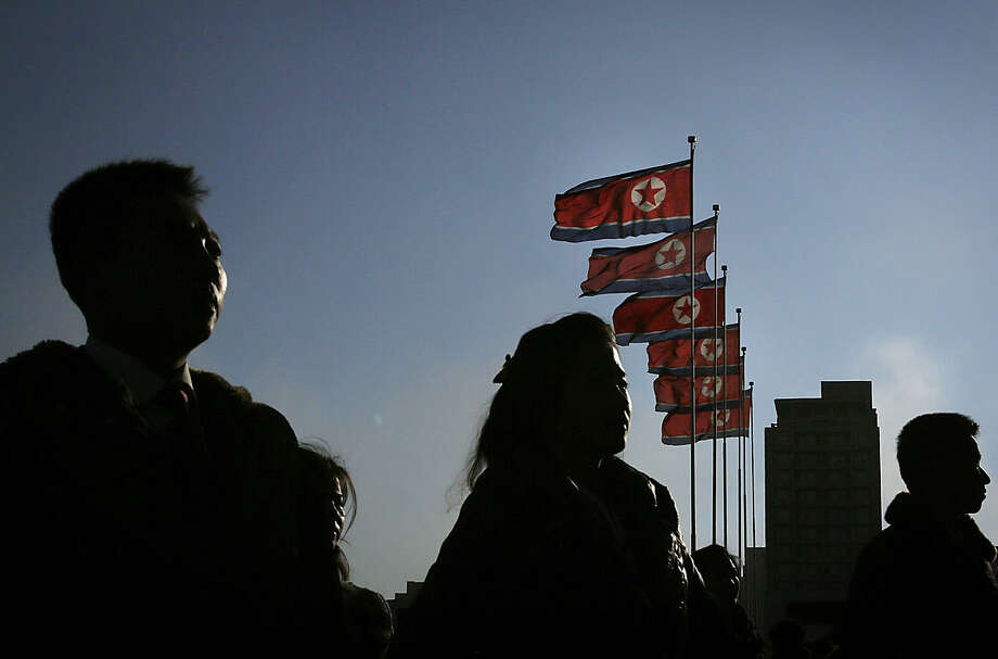 "North Korean men and women are silhouetted with their country's national flags in the background during a mass dance party as part of celebrations of the ""Day of the Shining Star"" or birthday anniversary of late North Korean leader Kim Jong Il on Tuesday, Feb. 16, 2016, in Pyongyang, North Korea. The celebrations of the Kim's birthday anniversary, a revered national holiday, came as South Korea's president warned that North Korea faces collapse if it doesn't abandon its nuclear weapons program, amid an international outcry over Pyongyang's January nuclear test and the Feb. 7 rocket launch. (AP Photo/Wong Maye-E)"