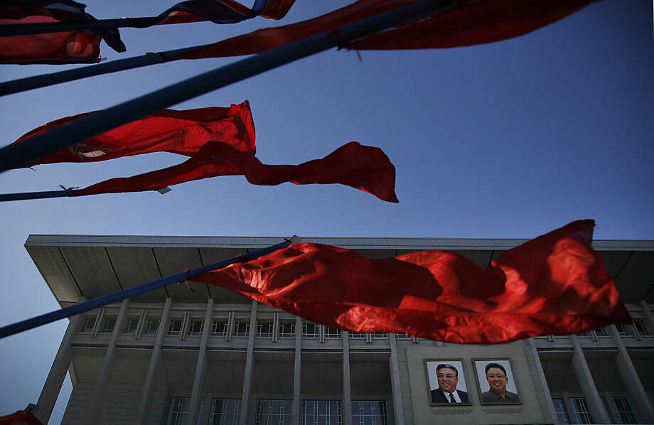 "Portraits of the late leaders Kim Il Sung, left, and Kim Jong Il, right, hung at the entrance of the Pyongyang Indoor Stadium are seen in the background as North Korean national flags and Youth League flags decorate the venue on the ""Day of the Shining Star"" or birthday anniversary of Kim Jong Il on Tuesday, Feb. 16, 2016, in Pyongyang, North Korea. The celebrations of the late Kim Jong Il's birthday anniversary, a revered national holiday, came as South Korea's president warned that North Korea faces collapse if it doesn't abandon its nuclear weapons program, amid an international outcry over Pyongyang's January nuclear test and the Feb. 7 rocket launch. (AP Photo/Wong Maye-E)"