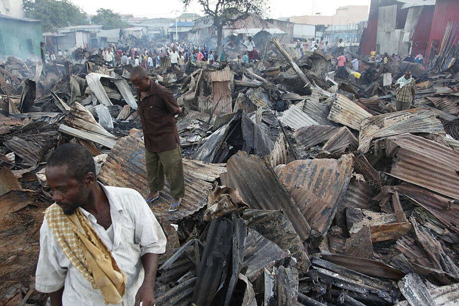 Somali shopkeepers stand on destroyed and burnt iron sheets after a fire gutted hundreds of shops and restaurants in the Wadajir district, in the capital Mogadishu, Somalia Tuesday, Feb. 16, 2016. (AP Photo/Farah Abdi Warsameh)