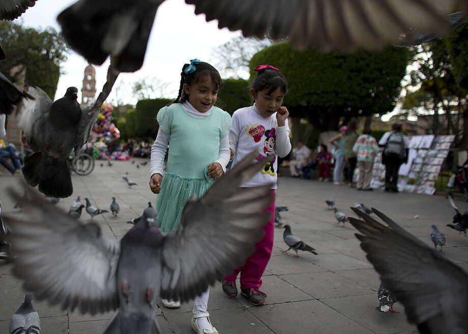 Girls chase pigeons in the Zocalo, or central square, in Morelia, Michoacan state, Mexico, Monday, Feb. 15, 2016. On his one-day trip Tuesday to the capital of troubled Michoacan state, Pope Francis will visit the cathedral, meet with youth, and celebrate Mass with priests and seminarians, and religious men and women.(AP Photo/Rebecca Blackwell)