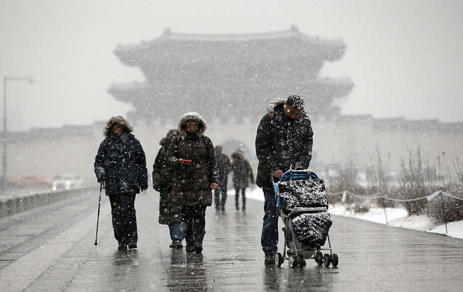 Visitors walk in the snow near the Gwanghwamun, the main gate of the 14th-century Gyeongbok Palace, one of South Korea's well known landmarks, in Seoul, South Korea, Tuesday, Feb. 16, 2016. (AP Photo/Lee Jin-man)
