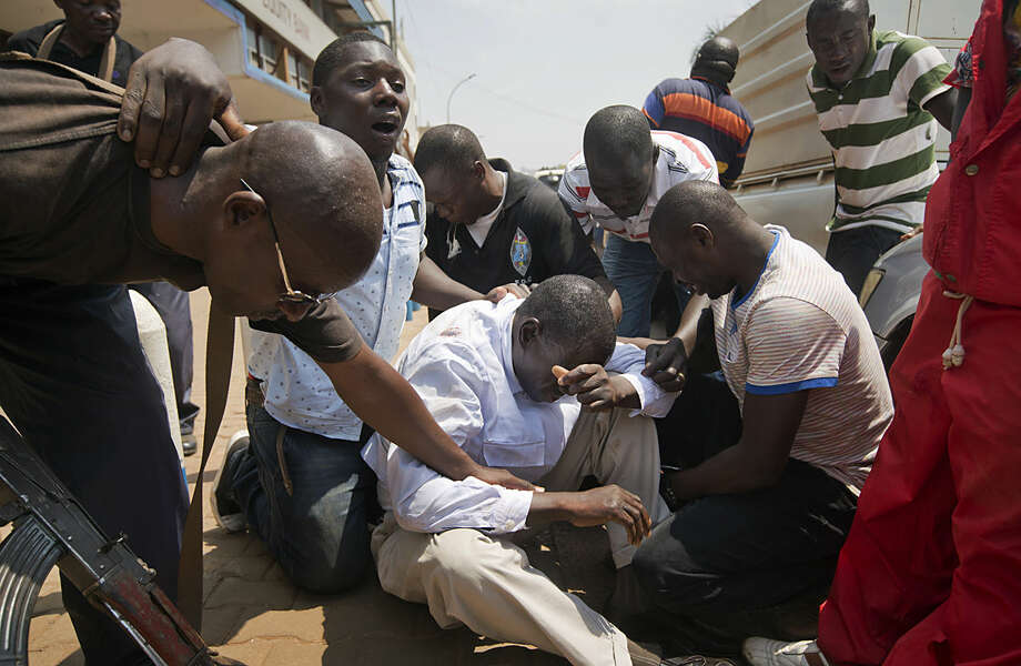 Leading opposition leader and presidential candidate Kizza Besigye, center, is surrounded by his bodyguards after being overcome by tear gas fired at him and his supporters by riot police, when they attempted to walk along a street in downtown Kampala, Uganda Monday, Feb. 15, 2016. Ugandan riot police arrested Besigye after tear-gassing him and his supporters when they tried to go from one election rally to another. (AP Photo/Ben Curtis)