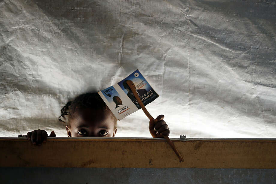 A child peeks through a classroom in a school set in the Mpoko refugee camp near the airport in Bangui, Central African Republic, Monday Feb. 15, 2016. Over 6000 children attend the school ran by a local NGO and funded by the UN. Two former prime ministers, Faustin Archange Touadera and Anicet Georges Dologuele, ran in the second round of presidential elections Sunday to end years of violence pitting Muslims against Christians in the Central African Republic. Central Africans will also vote in Legislative elections. (AP Photo/Jerome Delay)