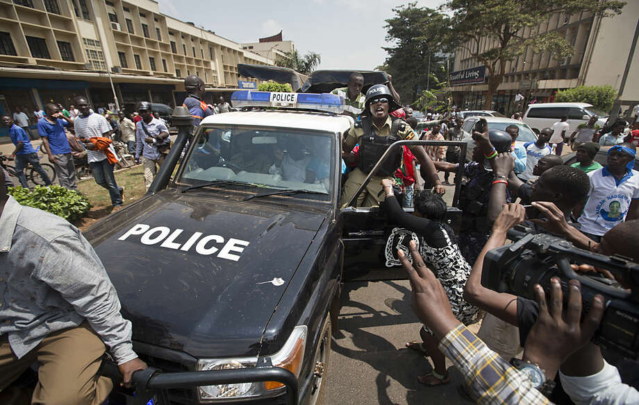 Leading opposition leader and presidential candidate Kizza Besigye, center, flashes the victory sign from the front seat of a police truck after being arrested by riot police when he attempted to walk with his supporters along a street in downtown Kampala, Uganda Monday, Feb. 15, 2016. Ugandan riot police arrested Besigye after tear-gassing him and his supporters when they tried to go from one election rally to another. (AP Photo/Ben Curtis)