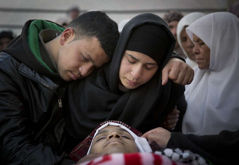Majd, 18, right and Musab, 22, left, mourn while taking the last look at their brother Naim Safi, 17, who was shot dead by Israeli forces last Sunday, at the family house during his funeral in the West Bank village of Abadiya, Bethlehem, Monday, Feb. 15, 2016. A Palestinian gripping a knife ran at Israeli border police officers at a West Bank checkpoint and an officer shot and killed him, no Israeli officers were wounded, Israeli police said. (AP Photo/Nasser Nasser)