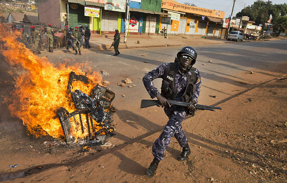 A Ugandan riot policeman runs past a burning barricade left by angry supporters of opposition leader Kizza Besigye, after he was prevented by police from reaching one of his campaign rallies, near to the Makerere University in Kampala, Uganda Monday, Feb. 15, 2016. Ugandan police fired tear gas and rubber bullets to break up the crowd of opposition supporters and briefly arrested Besigye himself on Monday, raising tensions ahead of elections widely seen as close. (AP Photo/Ben Curtis)