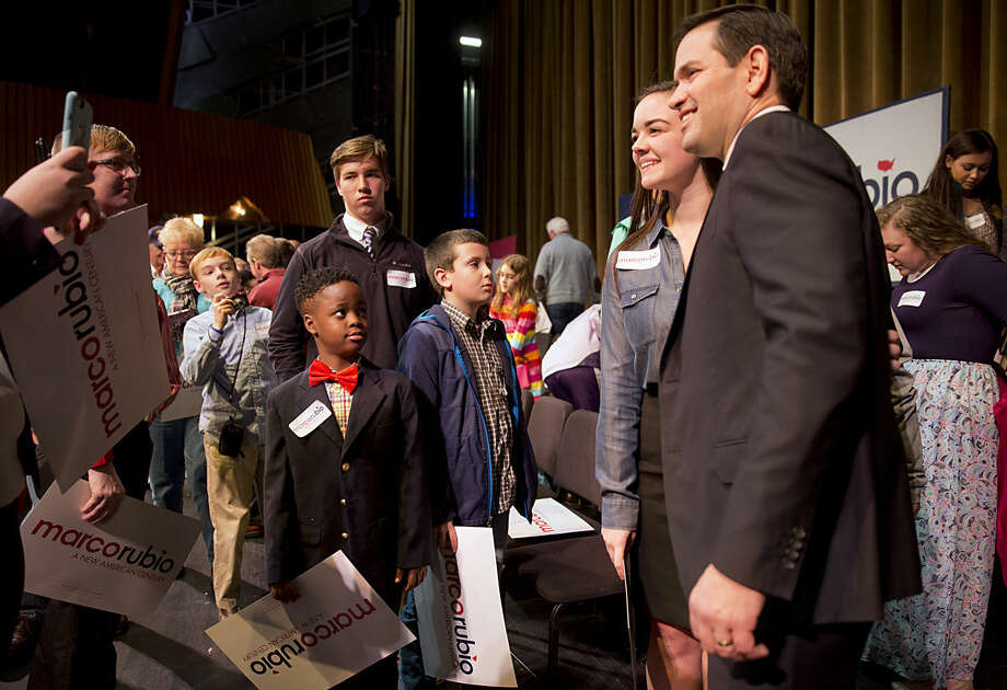 Tyler Merritts, 8, of Florence, S.C., left in red bow tie, watches as Republican presidential candidate Sen. Marco Rubio, R-Fla., takes pictures with supporter during a town hall meeting at Francis Marion University in Florence, S.C., Monday Feb. 15, 2016. Merritts' mother was in the audience and says that while she is still undecided that her son is definitely a Rubio fan. (AP Photo/Jacquelyn Martin)