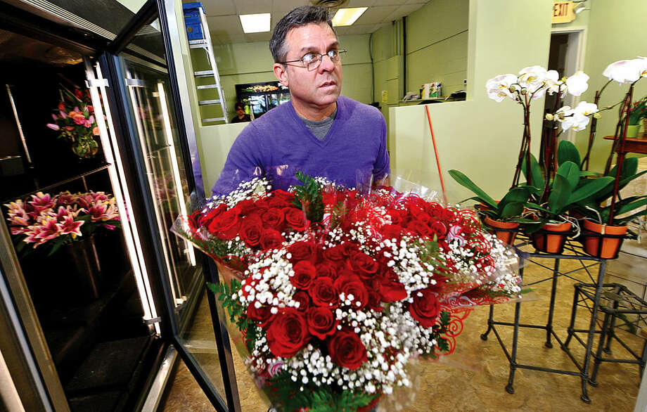 Hour photo / Erik Trautmann JP Licari works to ready the new location of his floral shop, Licari Floral Designs by JP, for Valentine's Day. Licari moved from Ludlow Plaza following a fire that gutted the shop to his new location at Cranbury Shopping Center.