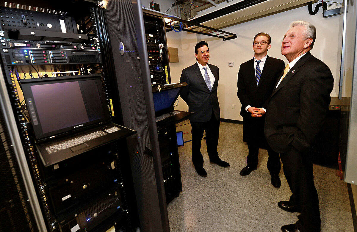 Hour photo / Erik Trautmann Apex Technology Services CEO, Rich Tehrani, and President, Larry Szebeni, give Norwalk Mayor Harry Rilling a tour of their server room as part of the mayor's small business intiative.
