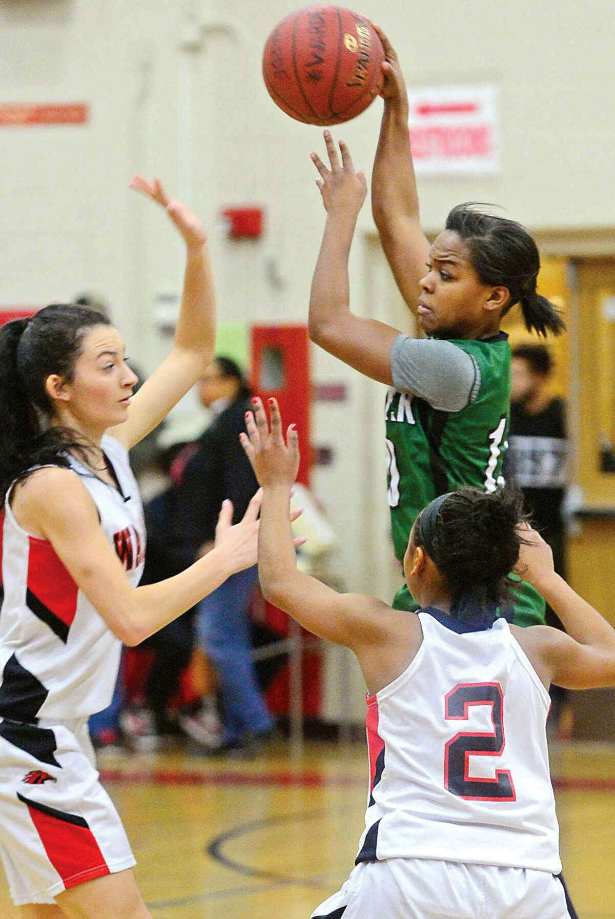 Hour photo / Erik Trautmann Norwalk High School Girls Basketball player #10 Jacqueline Harris looks to pass over Fairifeld Warde in the FCIAC quarter finals Saturday in Fairfield.