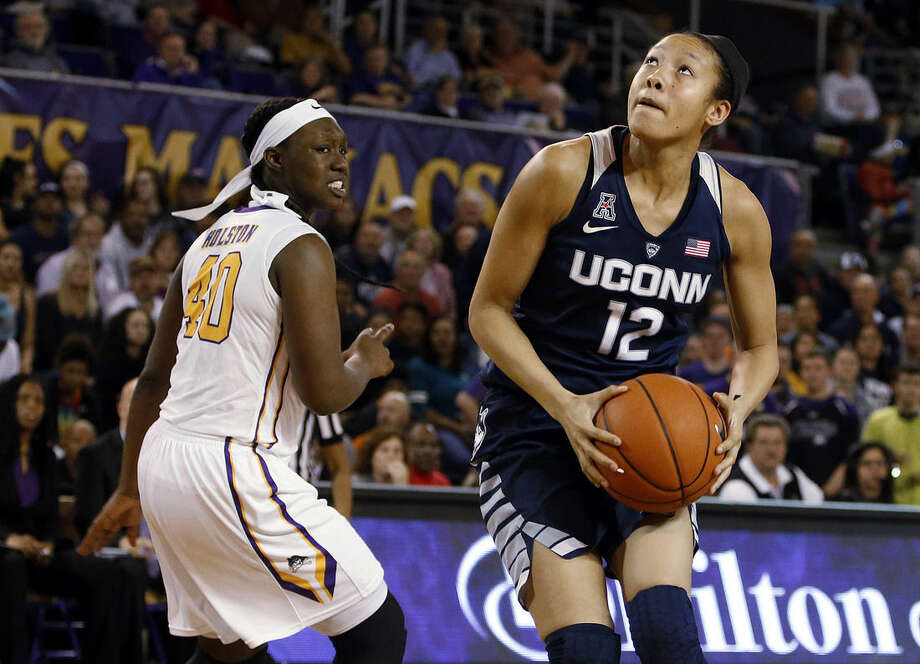 Connecticut's Saniya Chong (12) looks to shoot after dodging East Carolina's Gabrielle Holston (40) during the first half of an NCAA college basketball game Saturday, Feb. 20, 2016, in Greenville, N.C. (AP Photo/Karl B DeBlaker)