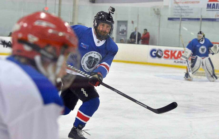 Hour Photo/Alex von Kleydorff Pete Paguaga defends against the white team as NY Rangers current players and alumni hold hockey clinics and take to the ice at SONO Ice House with 'NY Rangers Assist' program to benefit Hockey in Norwalk Foundation