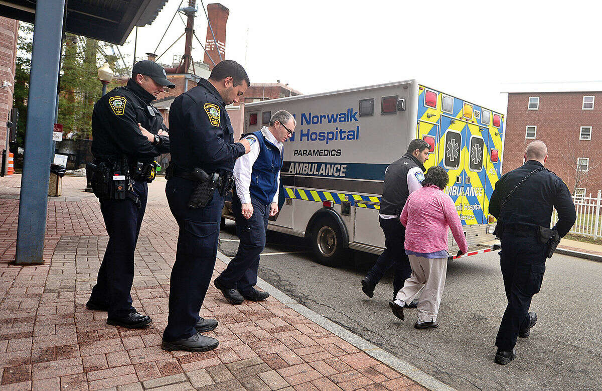 Hour photo / Erik Trautmann Emergency personnel escort a woman to an ambulance after she tried to jump onto the Metro-North train tracks at the South Norwalk station Wednesday afternoon.