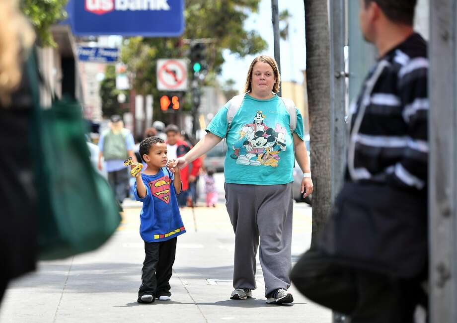 Angela Stephens walks with son Walter Hayes through the Mission District. Photo: Josh Edelson, The Chronicle