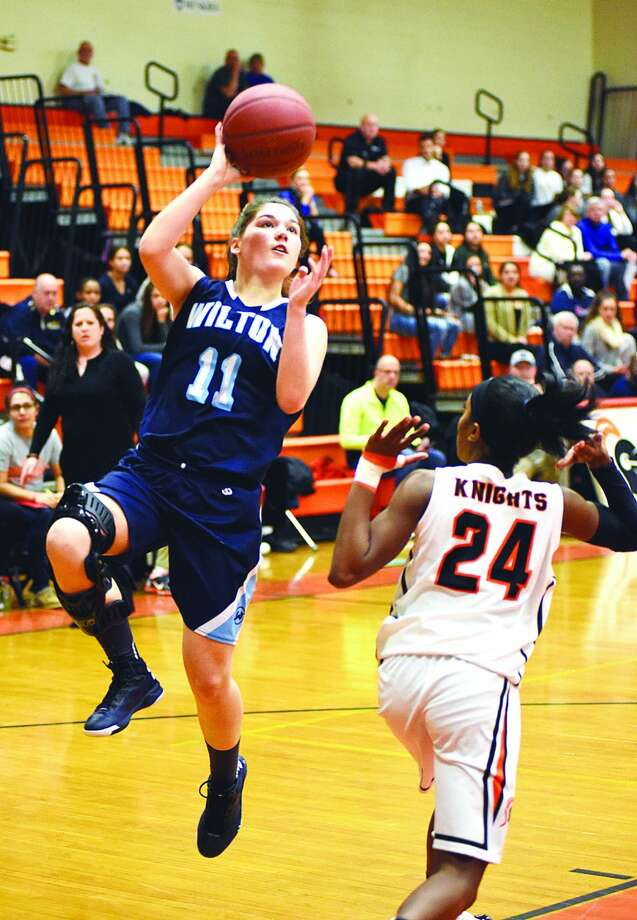 Wilton's Sarah Fitzgerald, left, puts up a shot after getting fouled by Stamford's Tiana England during Saturday's FCIAC girls basketball quarterfinal at Kuczo Gym in Stamford.