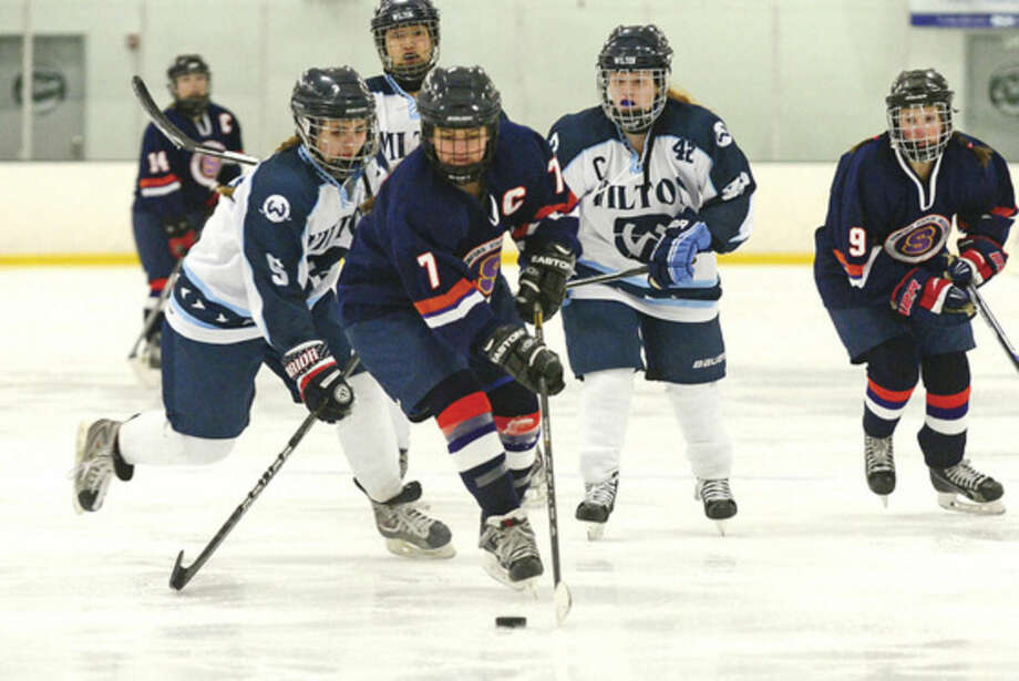 Hour photo/Erik TrautmannStaples-Westhill-Stamford girls hockey player Meg Fay (7) gathers up the puck against Wilton players Caroline Crupe (5) and Caroline Costello (42) during Saturday's game at the SoNo Ice House.