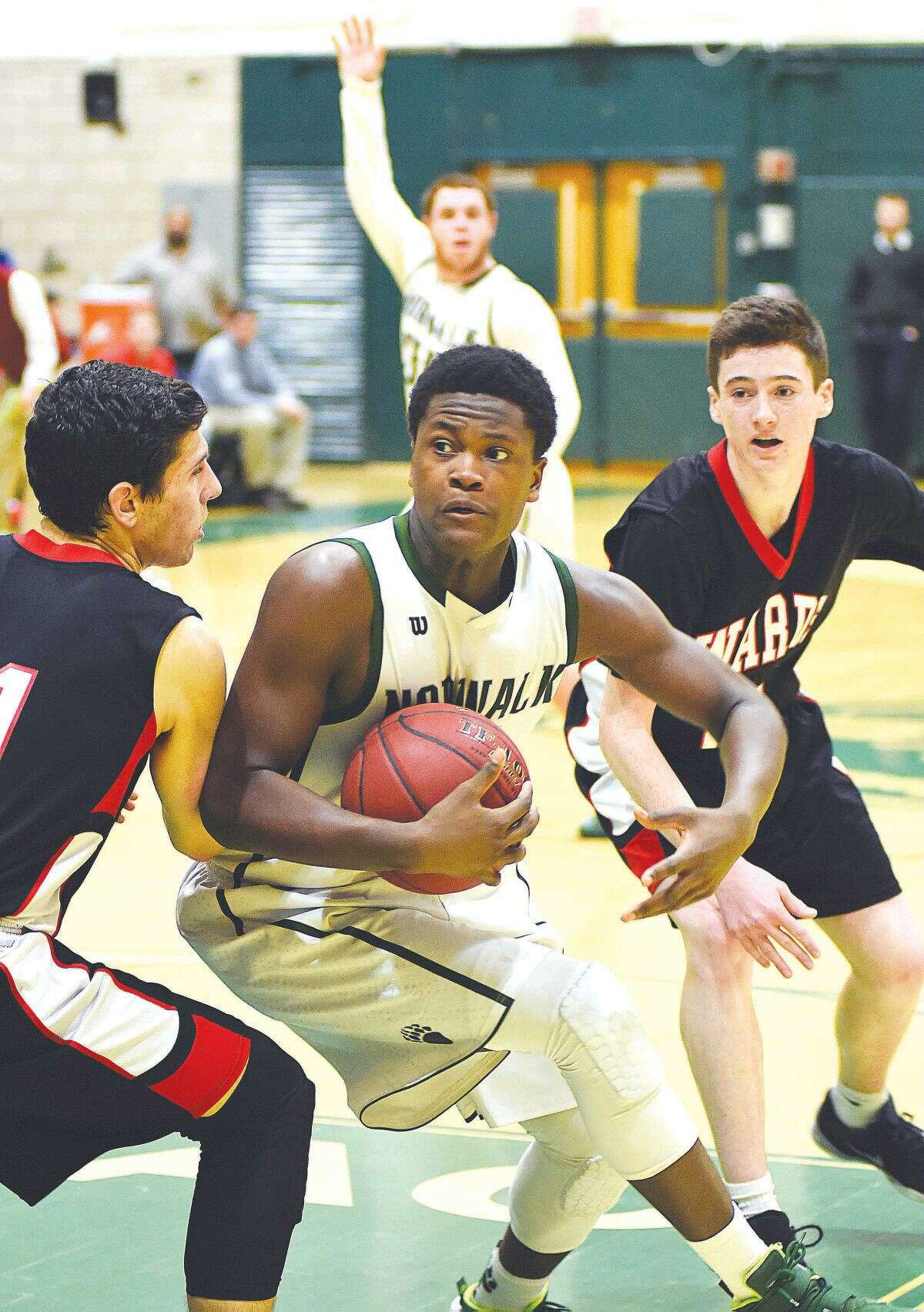 Hour photo/John Nash - Norwalk's LeVaughn Lewis, center, looks for space as Warde defenders move in during Monday's FCIAC boys basketball game at Scarso Gym in Norwalk.