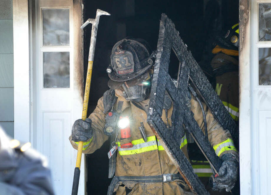 Wilton Firefighter Kevin Locher removes some debris to clear the entrance of a house on Valeview Road in Wilton on Tuesday. Emergency personnel responded to the house fire with mutual aid from Norwalk and were able to stop the fire quickly.