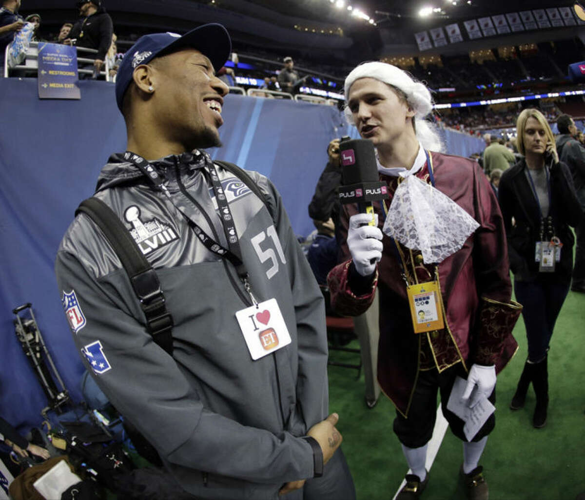 Phillip Hajszan interviews Seattle Seahawks' Bruce Irvin during media day for the NFL Super Bowl XLVIII football game Tuesday, Jan. 28, 2014, in Newark, N.J. (AP Photo/Charlie Riedel)