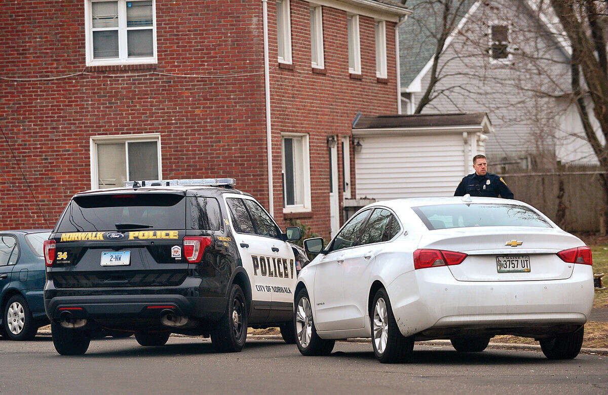 Hour photo / Erik Trautmann Norwalk police search for a suspect at Colonial Village after a stolen motor vehicle was recovered nearby on Tuesday morning.