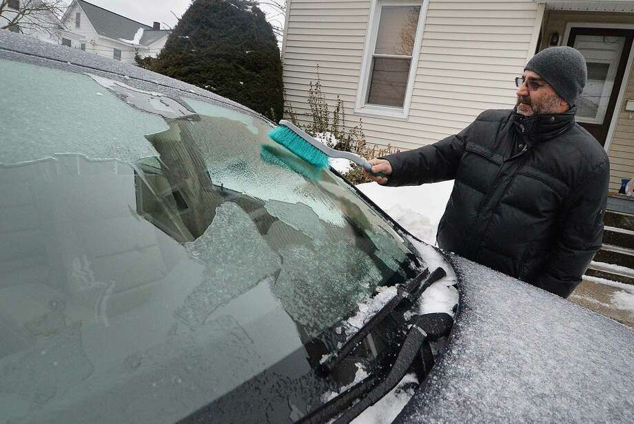 Hour Photo/Alex von Kleydorff Mike Gavrielidis uses the brush end of his broken scraper and the defroster on high to clear a sheet of ice on the windshield of his car on Monday morning in Norwalk
