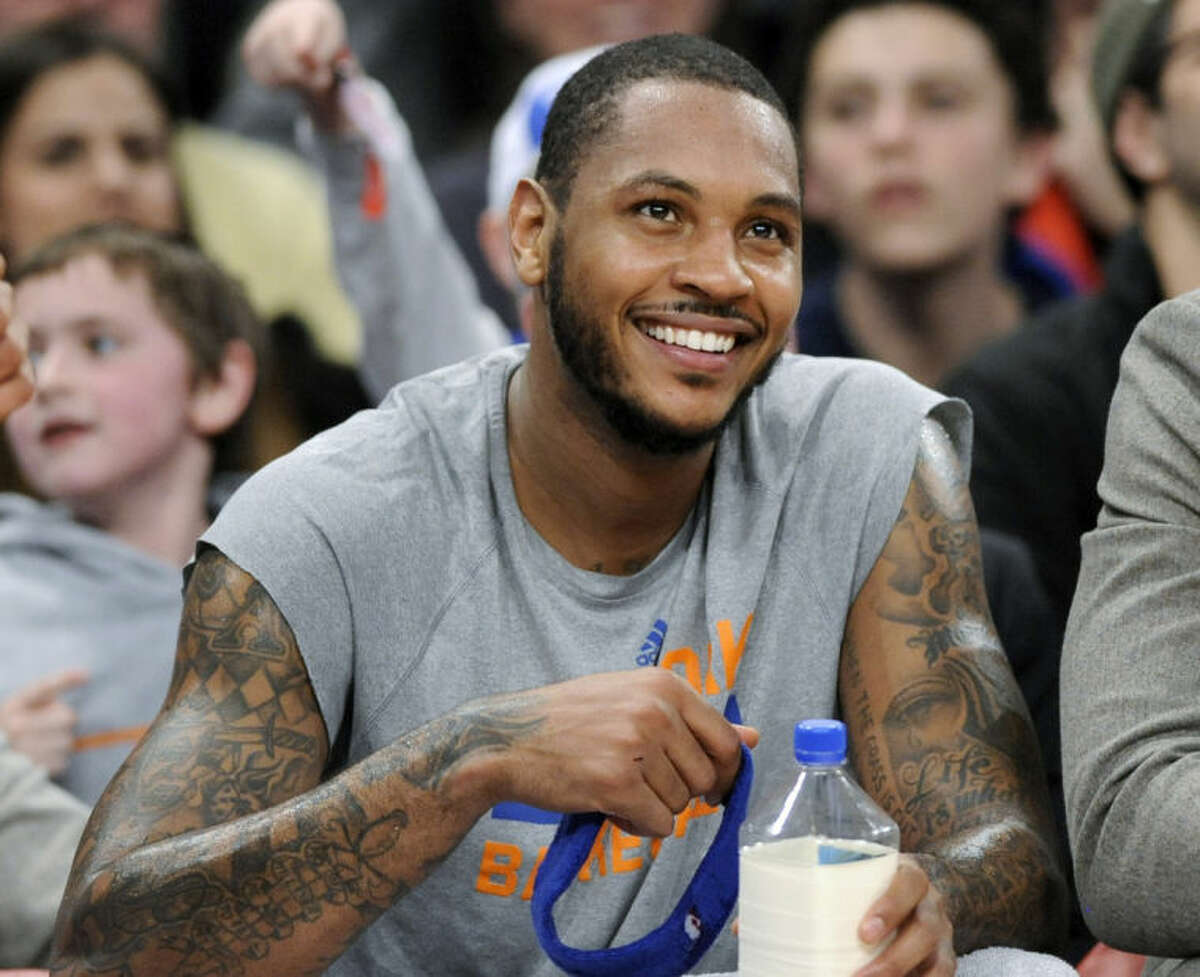 FILE - In this Jan. 24, 2014 file photo, New York Knicks' Carmelo Anthony smiles as he watches from the bench during the fourth quarter of an NBA basketball game against the Charlotte Bobcats, at Madison Square Garden in New York. Signing day has arrived in the NBA, if the biggest free agents care to grab their pens. But it?'s unclear if Anthony, Chris Bosh and Dwyane Wade _ who all might be waiting on LeBron James to go first _ are ready. (AP Photo/Bill Kostroun, File)