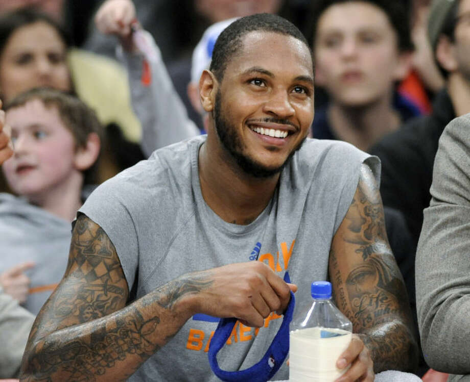 FILE - In this Jan. 24, 2014 file photo, New York Knicks' Carmelo Anthony smiles as he watches from the bench during the fourth quarter of an NBA basketball game against the Charlotte Bobcats, at Madison Square Garden in New York. Signing day has arrived in the NBA, if the biggest free agents care to grab their pens. But it's unclear if Anthony, Chris Bosh and Dwyane Wade _ who all might be waiting on LeBron James to go first _ are ready. (AP Photo/Bill Kostroun, File)