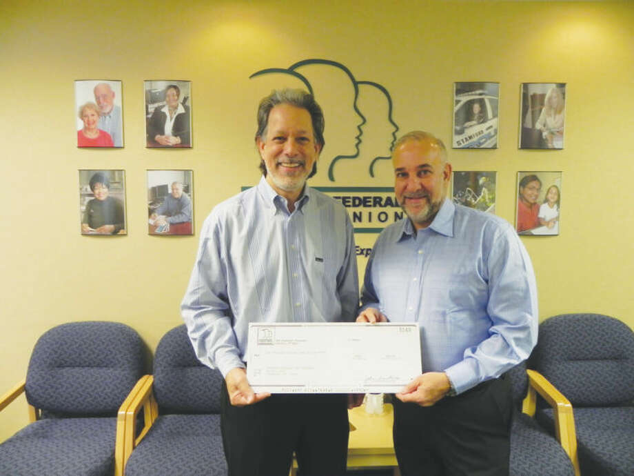 David Lucas (pictured at right), president and CEO of the Stamford Federal Credit Union, hands an oversized check to Tony D'Amelio, co-president of Stamford Dollars for Scholars, a local nonprofit that awards scholarships to Stamford students.