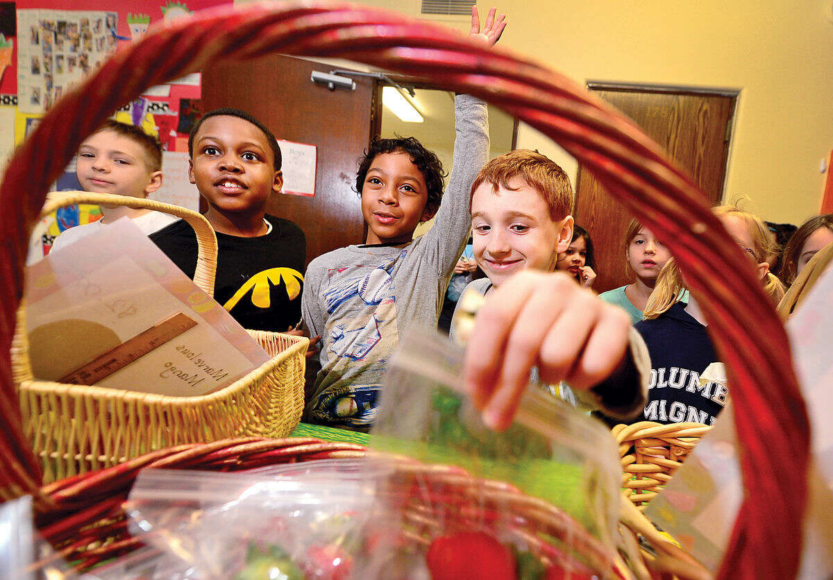 Hour photo / Erik Trautmann Columbus Magnet School students Devin Eason, Amir Miquel Walker-Silva and Jordan Bagnara shop for produce during the school's annual Berry-Go Round First Grade Market. Each year the First Grade hallway is transformed into a produce market offering fresh fruits and vegetables for purchase from the enterprising first graders.