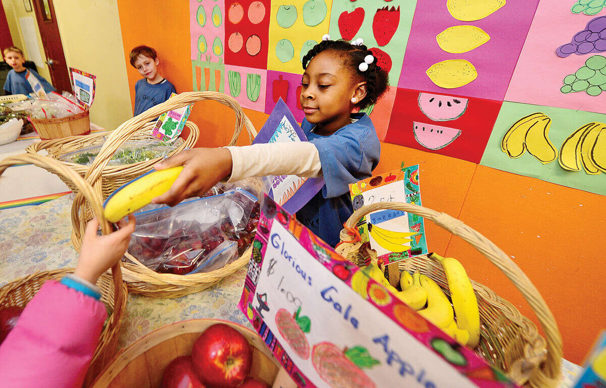 Hour photo / Erik Trautmann Columbus Magnet School first grader Nariah Jonas sells bananas during the school's annual Berry-Go Round First Grade Market. The First Grade hallway is transformed into a produce market offering fresh fruits and vegetables for purchase from the enterprising first graders.