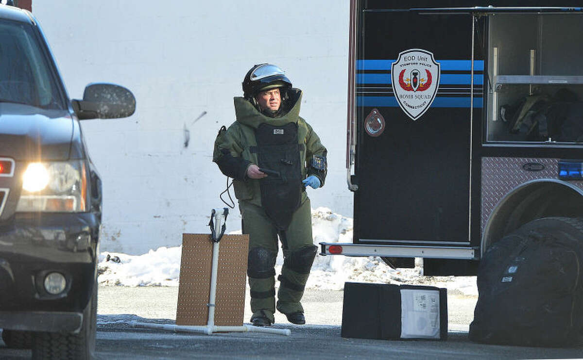 Hour Photo/Alex von Kleydorff A member of the Stamford Bomb Squad exits Puppies of Westport with what appears to be a cell phone in his hand after being called to investigate the suspicious device
