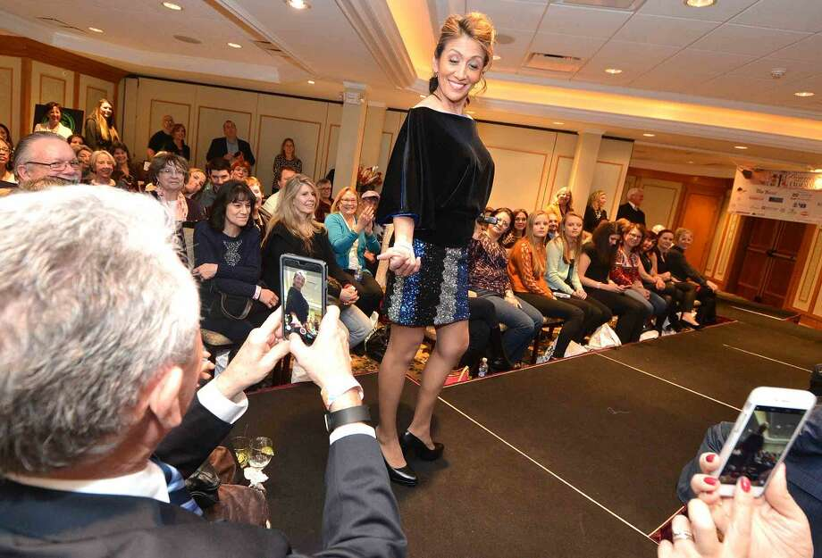 Hour Photo/Alex von Kleydorff Lucia Rilling on the runway wearing a Jennifer Butler original while husband Harry Rilling shoots some video during the fashion show at The Hour's 3rd annual Beauty and the Bubbly evening at The Norwalk Inn