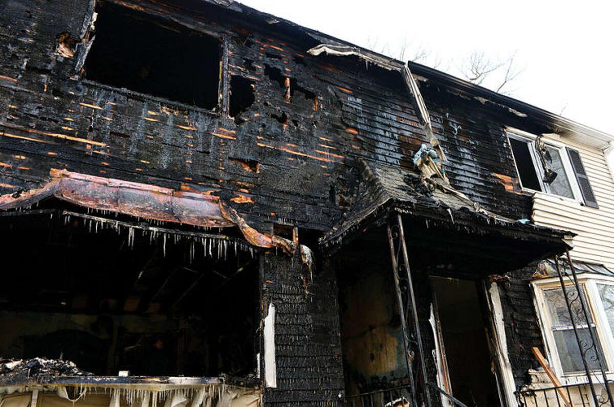 Hour photo / Erik Trautmann Norwalk fire inspectors comb through tthe duplex gutted by fire at 2am Friday morning.