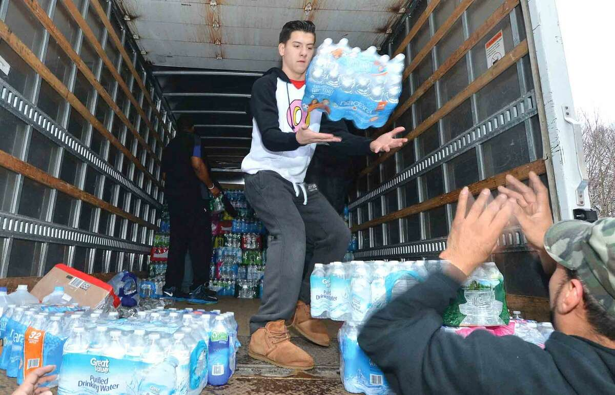 Hour Photo/Alex von Kleydorff Volunteers from All American Tree Service and Complete landscaping along with students from Brien McMahon High toss cases of water to be stacked in the back of a truck for a trip to Flint Michigan