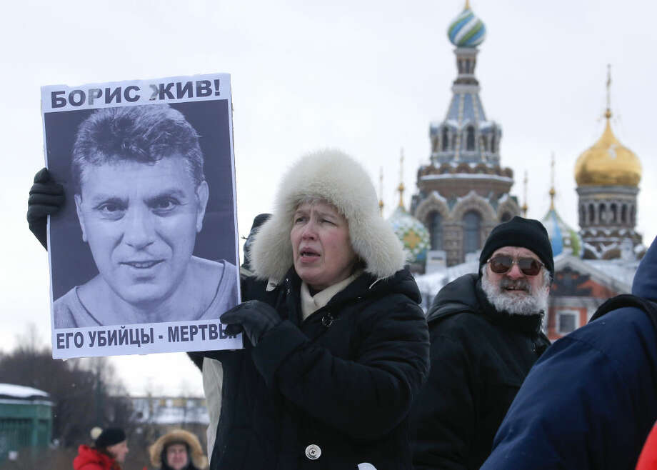 People gather to commemorate the 2015 slaying of opposition leader Boris Nemtsov, in St. Petersburg, Russia, Saturday, Feb. 27, 2016. The opposition held rallies across Russia on Saturday to commemorate one year since Nemtsov, a former deputy prime minister, was gunned down just outside the Kremlin. The sign reads: 'Boris is alive, his killers are dead'. (AP Photo/Dmitri Lovetsky)