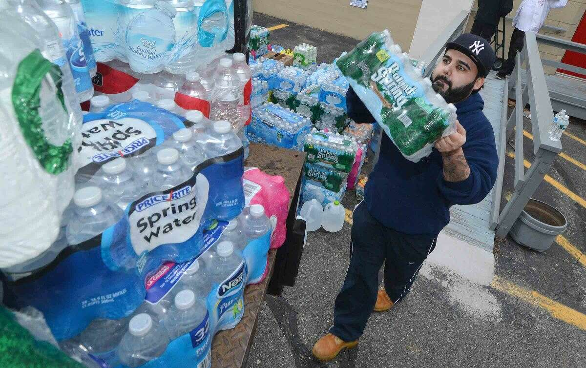 Hour Photo/Alex von Kleydorff Amir Khan one of the organizers of the water drive with help from volunteers to load some 1,500 cases of bottled water from a drop off point at Christ Episcopal Church into a box truck, to be driven to Flint Michigan